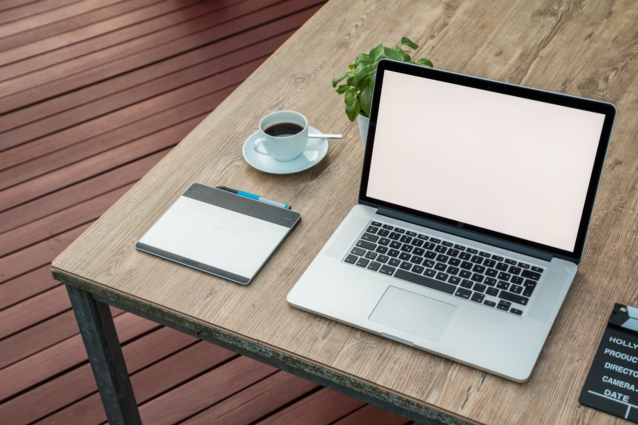Laptop on wooden desk with tea and pad of paper